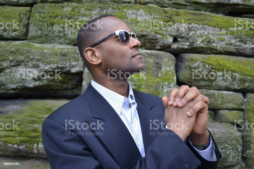 Model wearing a business suit,collared dress shirt and shades: Brick Wall stock photo