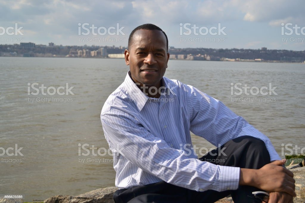 Model wearing a collared dress shirt and Riverside NY in the background stock photo