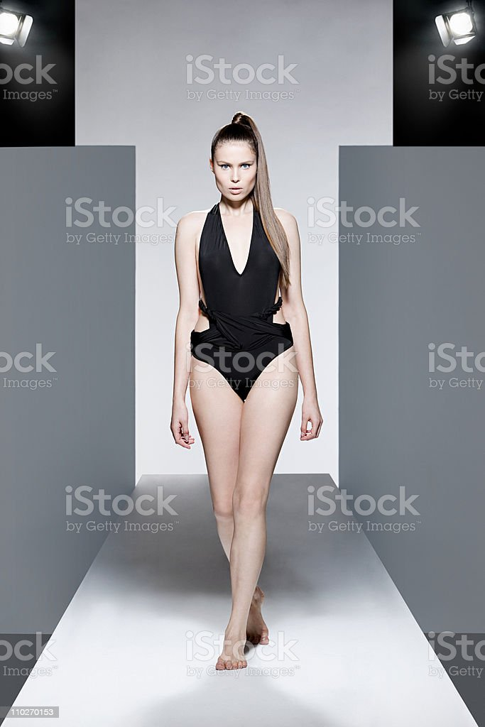 Model wearing black swimsuit on catwalk at fashion show stock photo