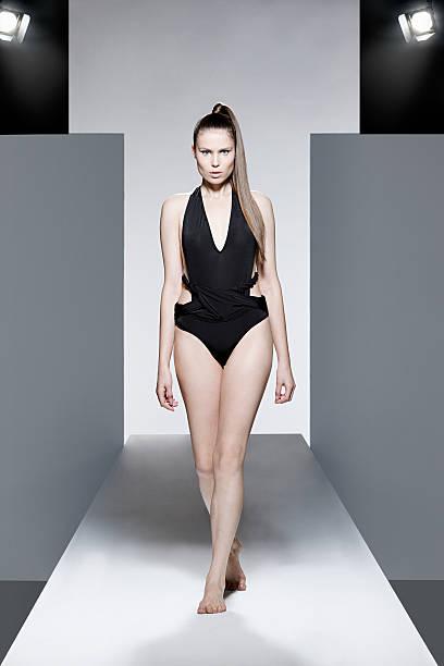 Model wearing black swimsuit on catwalk at fashion show stock photo