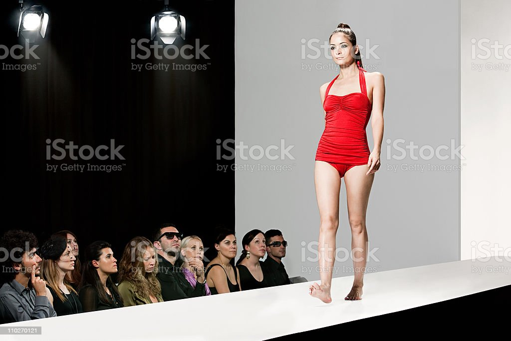 Model wearing red swimsuit on catwalk at fashion show stock photo