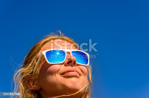 A blonde haired female model wearing sunglasses with blue lenses against a blue sky background.