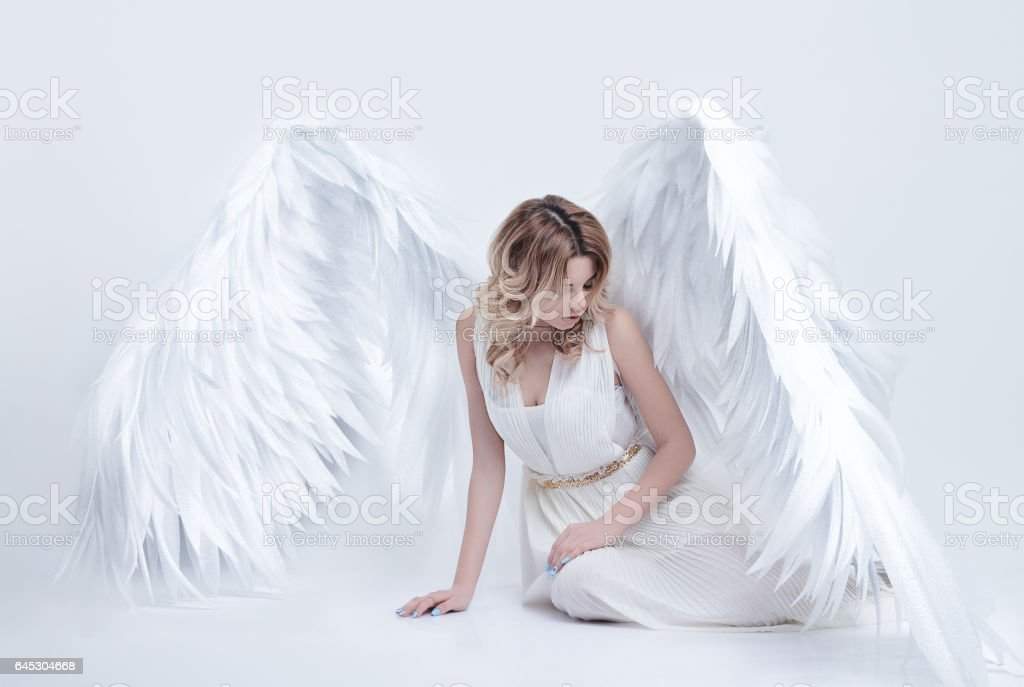 model with big angel wings sitting in the studio stock photo