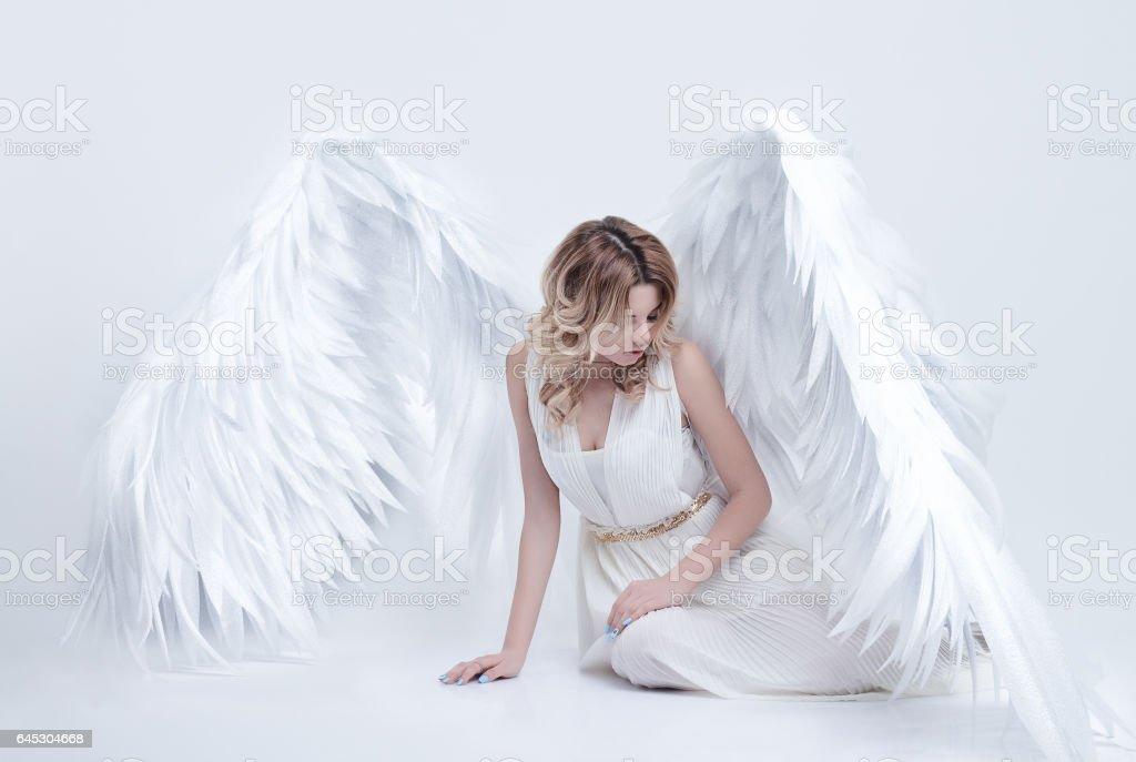 modèle avec des ailes d'ange grand assis dans le studio - Photo