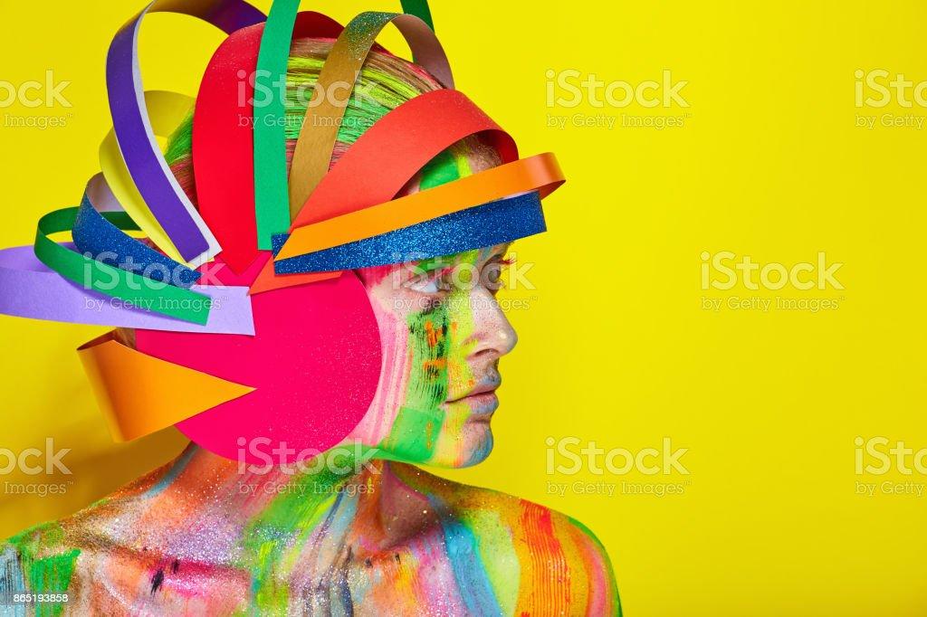 Modelo com maquiagem abstrata colorida no capacete multicolorido - foto de acervo