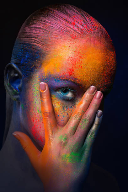 Model with colorful art make-up, close-up Holi colours festival. Portrait of model with colorful makeup posing on dark studio background. Abstract art make-up, crop body paint stock pictures, royalty-free photos & images