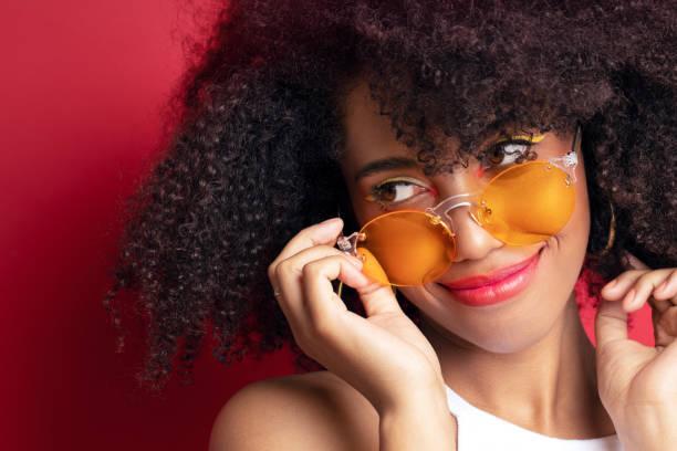 model with dark curly hair in orange glasses stock photo