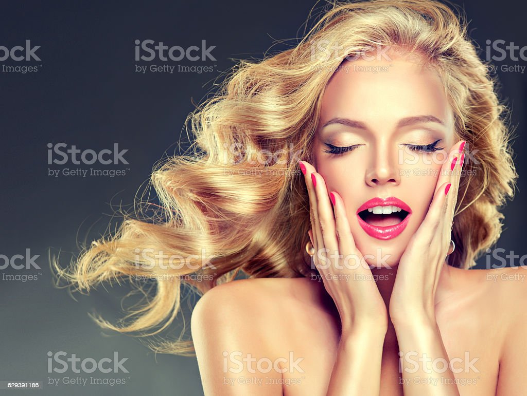 Model with flying wavy, dense blond hair. stock photo