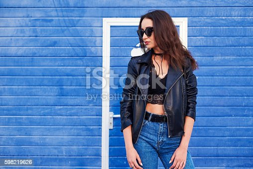 fashion model with long curly hair wearing sunglasses posing outdoor. Jeans, leather jacket.model with long curly hair posing outdoor. Jeans, leather jacket.