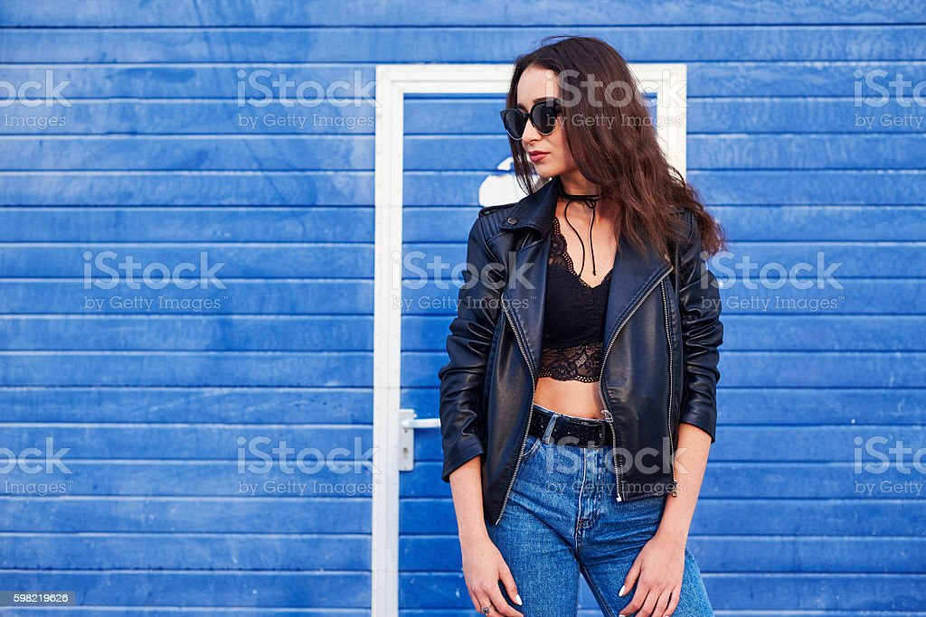 model with long curly hair posing outdoor. Jeans, leather jacket. stock photo