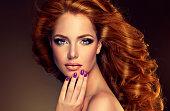 モデル、長いカーリーレッドヘアとパープルの爪を美しく整えます。