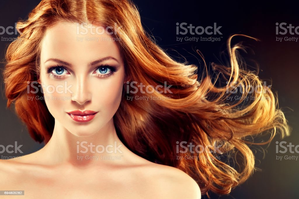 Model with long, dense and curly hairstyle. Red hair. stock photo