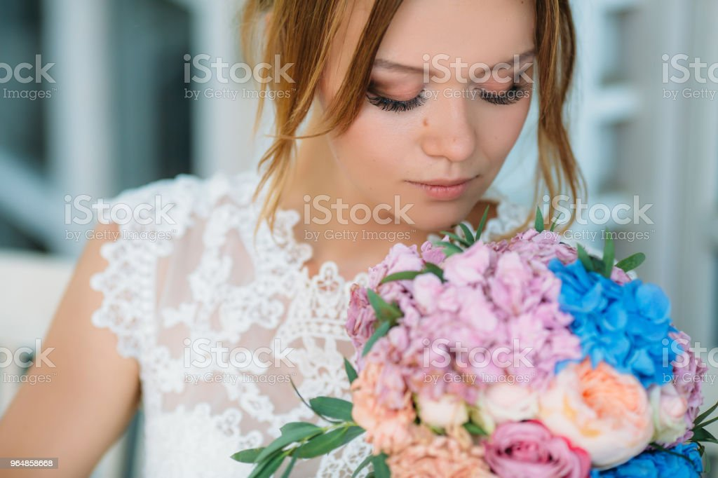 A model with makeup in natural colors and large eyelashes looks at a bouquet of flowers. A beautiful girl inhales the aroma of roses and peonies royalty-free stock photo