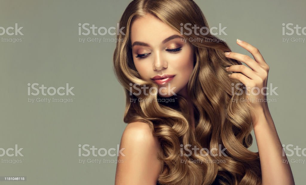 Young, woman with deep blonde,voluminous and frizzy hair.Model with...
