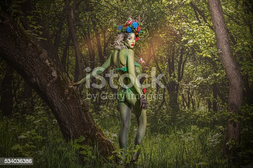 Young model woman in the form of a nymph among the trees unusual fancy patterns on the body