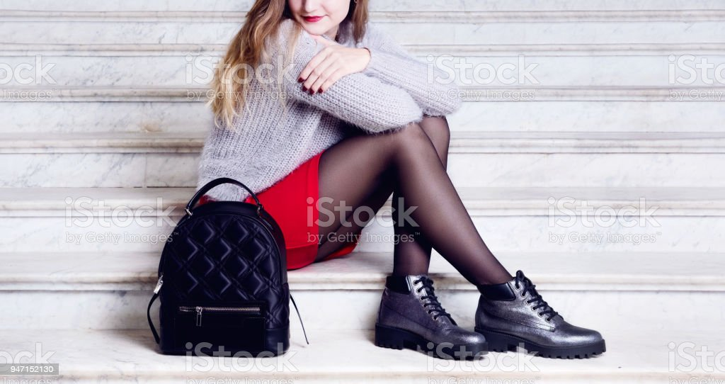 Model woman legs in black boots with bag. stock photo