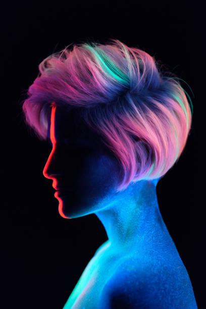 模特年輕漂亮的女孩肖像在工作室與創意化妝, 在霓虹燈紫外線燈。在黑暗中發光。頭髮著色與霓虹燈油漆。身體藝術是藍色, 綠色, 橙色 - 霓虹色 個照片及圖片檔