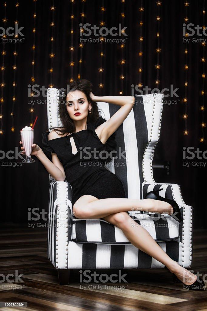 Modelo de mulher jovem bonito e luxuoso, sentado em uma cadeira listrada preto e branca na moda e elegante - foto de acervo