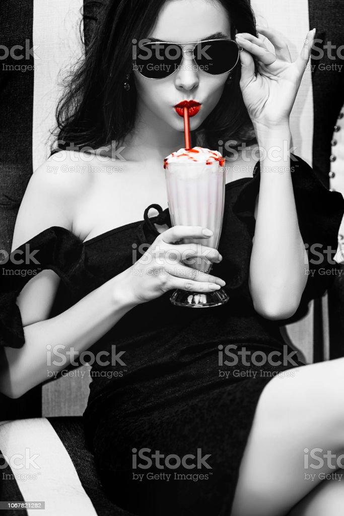 Modelo de mulher jovem bonito e luxuoso sentado com morango cocktail no elegante cadeira listrado preto e branco e elegante em óculos de sol - foto de acervo