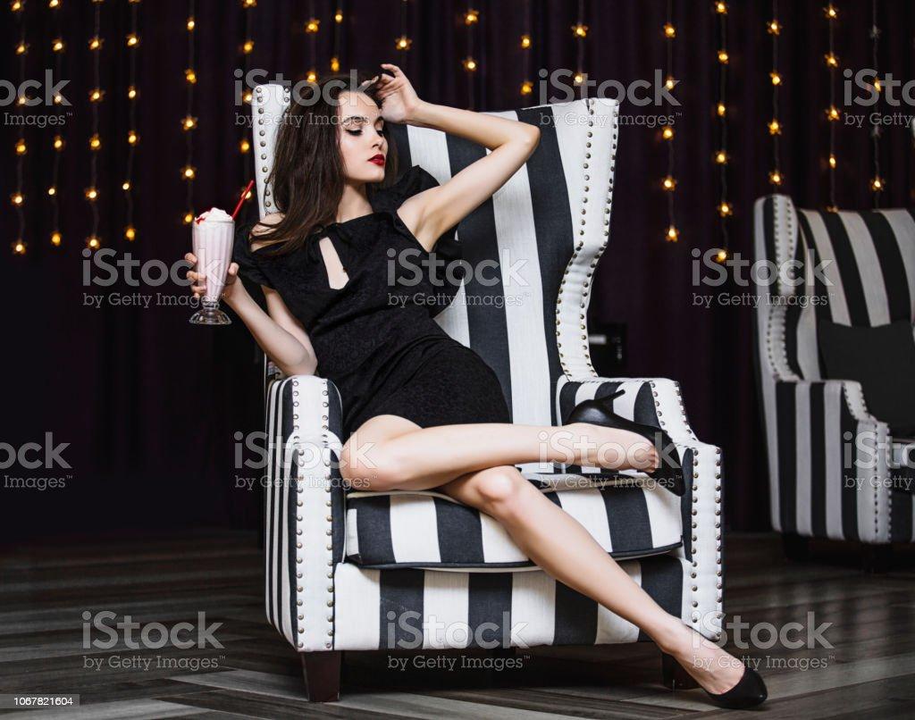 Modelo de mulher jovem bonito e luxuoso sentado com morango cocktail no elegante cadeira listrado preto e branco e elegante - foto de acervo