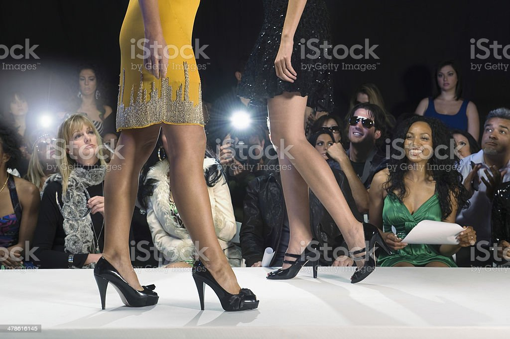 Models In High Heels Against Spectators stock photo