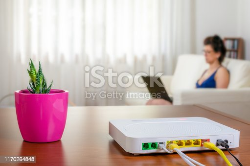 Modem router on a table in a living room. A woman using a laptop while sitting on the sofa is in background. Selective focus.