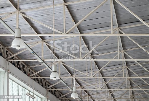 Moden electrical lamp is hanging on the steel beam of the warehouse.
