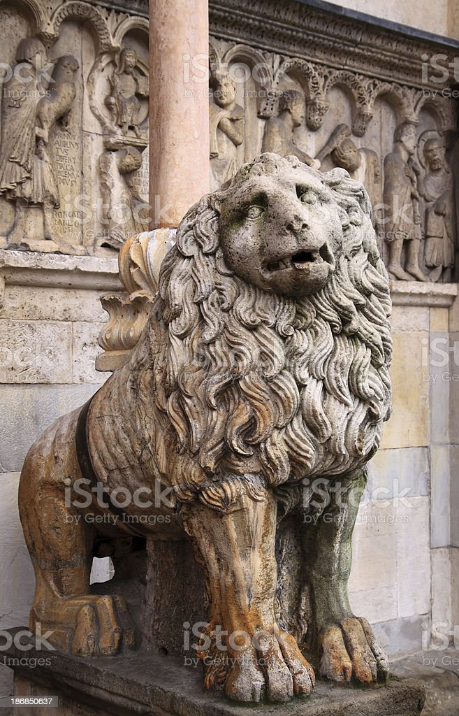 Modena, Cathedral: lion statue and reliefs by Wiligelmus royalty-free stock photo