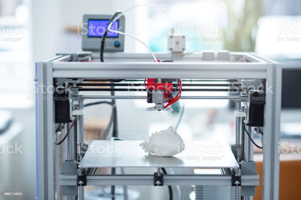Modern 3D printer creating model of heart stock photo