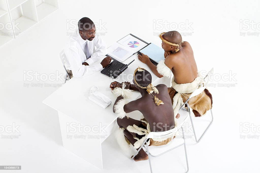 modern african businessman consulting with tribal clients royalty-free stock photo