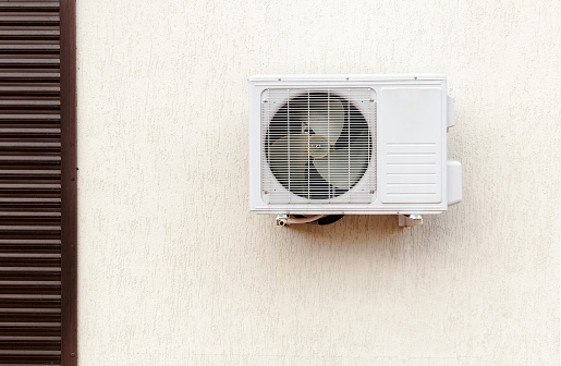 istock Modern air conditioner compressoron a light wall of office building 947099530