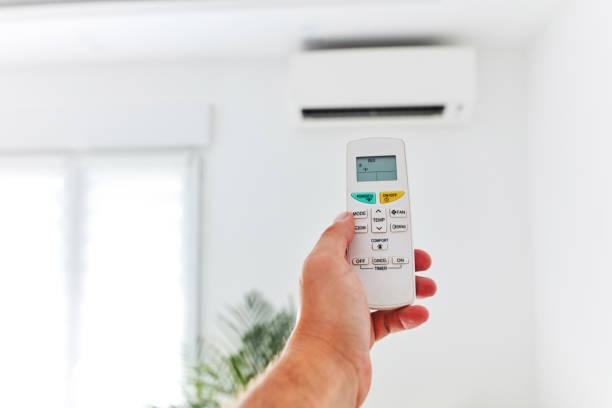 Moderne Klimaanlage Einheit mit einer Hand hält eine Fernbedienung. – Foto