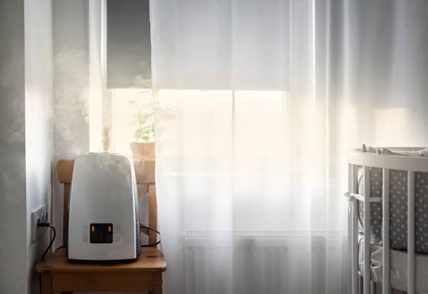 子供部屋の窓に近いモダンな空気加湿器。健康と空気の浄化。 - 加湿器 ストックフォトと画像