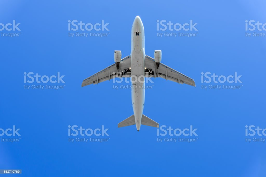 modern airplane is flying in a blue sky, close-up stock photo