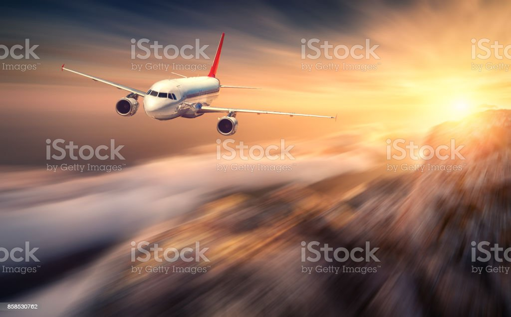 Modern airplane mith motion blur effect is flying over low clouds at sunset. Landscape with passenger airplane, blurred clouds, mountains, sun. Passenger aircraft. Business travel. Commercial plane stock photo