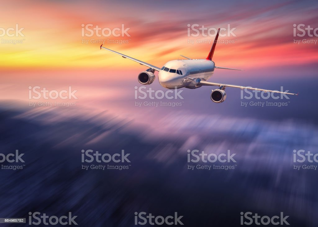 Modern airplane mith motion blur effect is flying over low clouds at sunset. Landscape with passenger airplane, blurred clouds, sunlight in dusk. Passenger aircraft. Business travel. Commercial plane stock photo