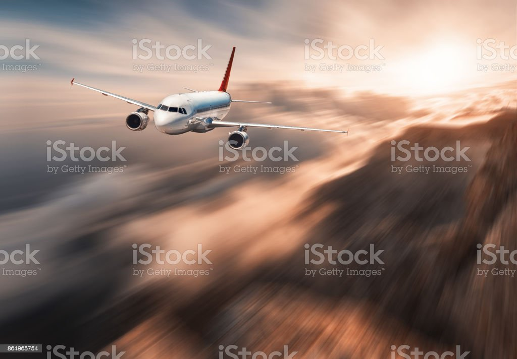 Modern airplane mith motion blur effect is flying over low clouds at sunset. Landscape with passenger airplane, blurred clouds, mountains, sun. Passenger aircraft. Commercial plane. Vintage style stock photo