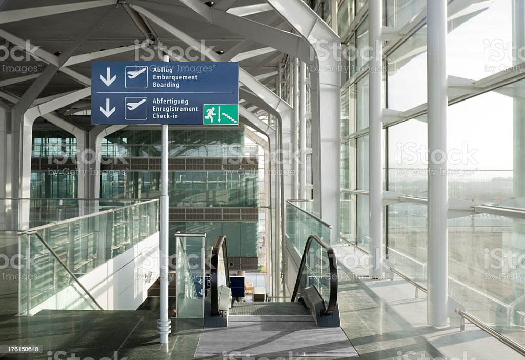 Modern Airport Departure Hall with Escalators and Glass Windows royalty-free stock photo