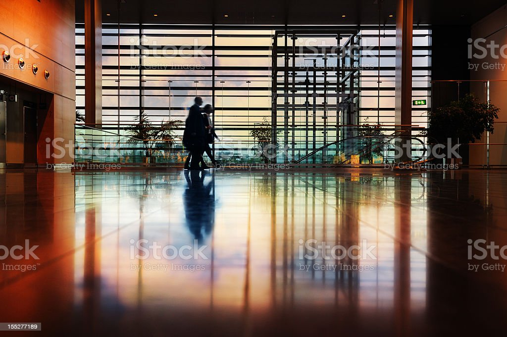Modern airport terminal, travellers in silhouette royalty-free stock photo