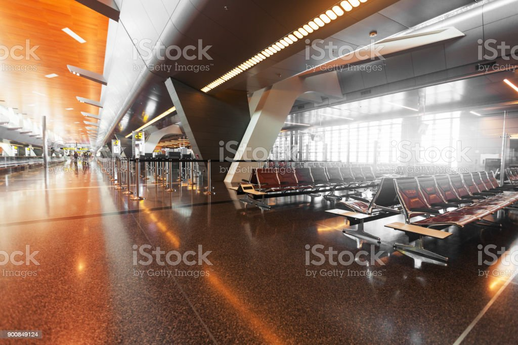 modern airport terminal with black leather seats at sunset. stock photo
