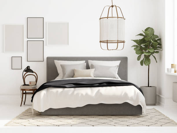 Modern all white Scandinavian bedroom with blank frames and ficus plant stock photo