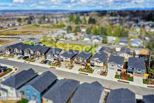 Tilt-shift photo of a modern American suburban neighborhood, shot from an aerial perspective
