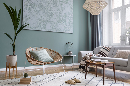 Modern and bohemian composition of interior design with gray sofa, rattan armchair, retro footrest, plaid, pillow, tropical plants, small table and elegant accessories. Stylish home decor. Template.