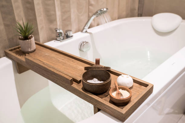 현대적이고 편안한 욕실, 나무 테이블과 세면도구가있는 욕조, 소금, 허브, 목욕 폭탄. - 욕조 뉴스 사진 이미지