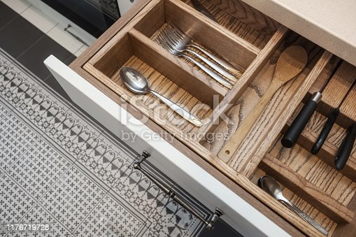 High angle view of house with modern interior design at kitchen. Top view of open drawer with wooden texture and silver cutlery supply