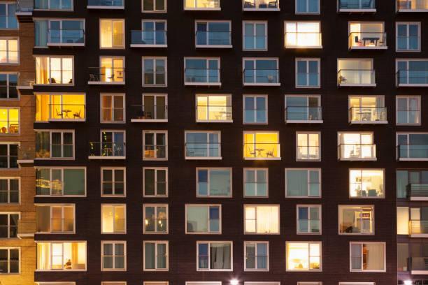 nowoczesny blok mieszkalny o zmierzchu - okno zdjęcia i obrazy z banku zdjęć