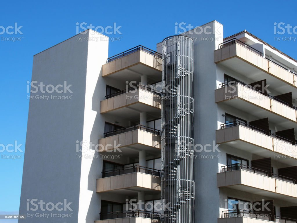 modern apartment block with circular metal fire escape with spiral stairs and angular stylish balconies stock photo