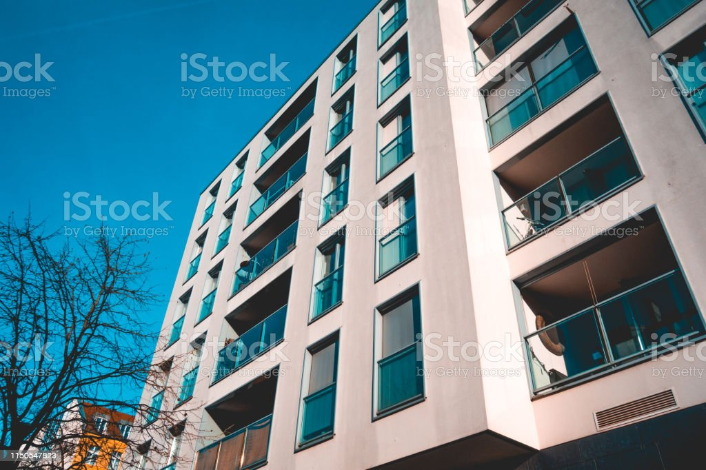 modern apartment building with glass balcony and darken sky