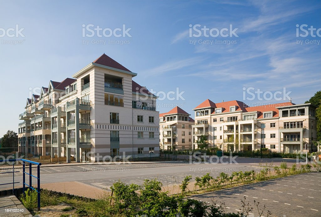 Modern apartment complex with parking lot under blue sky Site with brand new contemporary apartment buildings. Apartment Stock Photo
