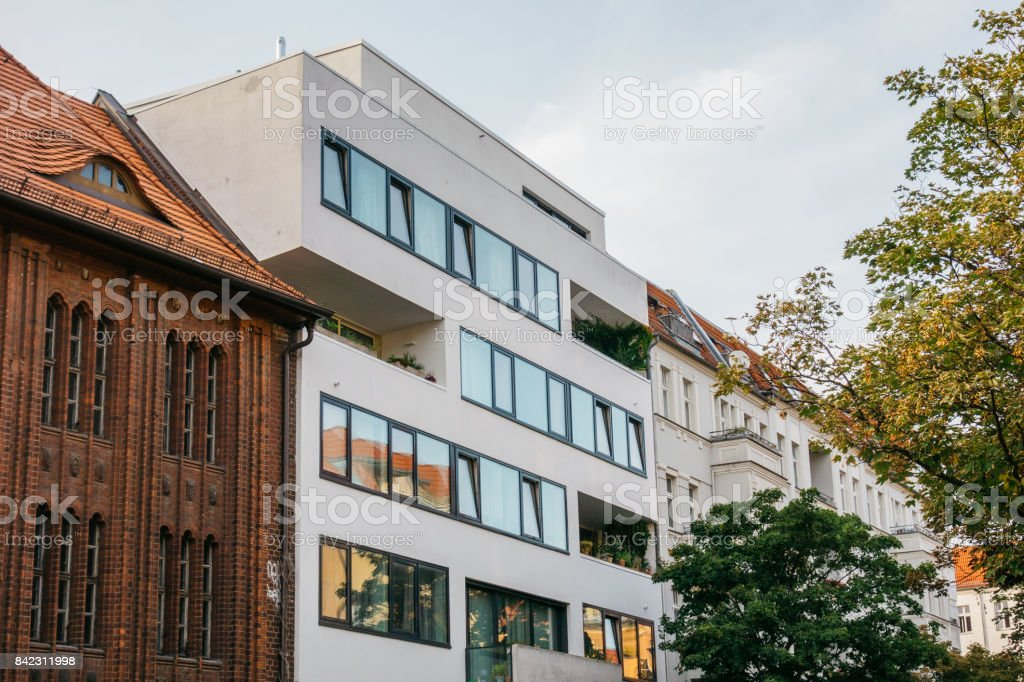 modern apartment or office building inbetween of old houses stock photo